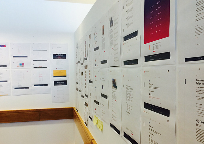 A photograph of two walls papered in printouts of modules and naming discussions.
