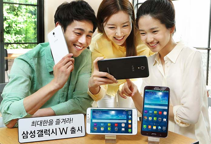Photograph showing three people operating phablets.