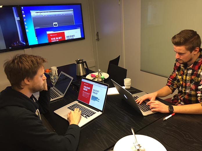 Two men sitting at a table and working on laptops, with a large screen in the background to display what they are collaborating on
