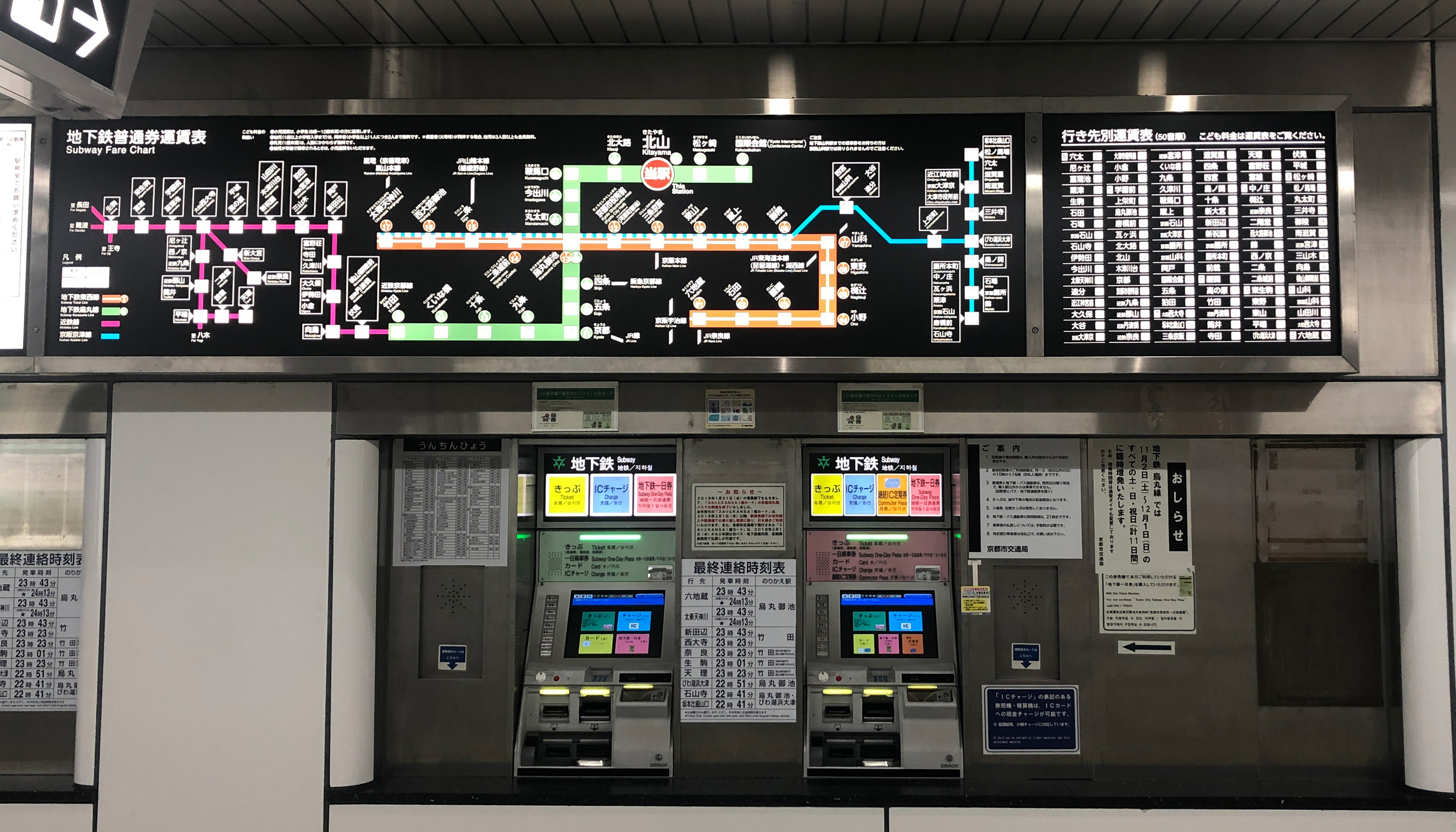 Photo of two subway ticket machines with complex maps above them